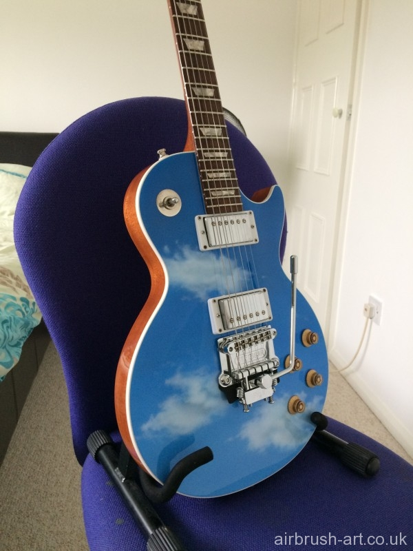 Gibson guitar sprayed sky blue with airbrushed white clouds. Guitar has been given a neat white edge.
