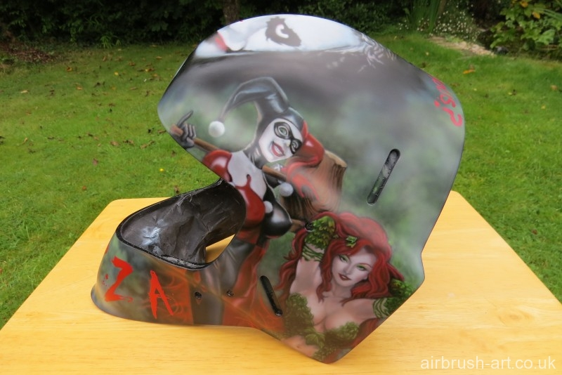 Poison Ivy and Harley Quin women airbrushed on side of hockey goalie mask.