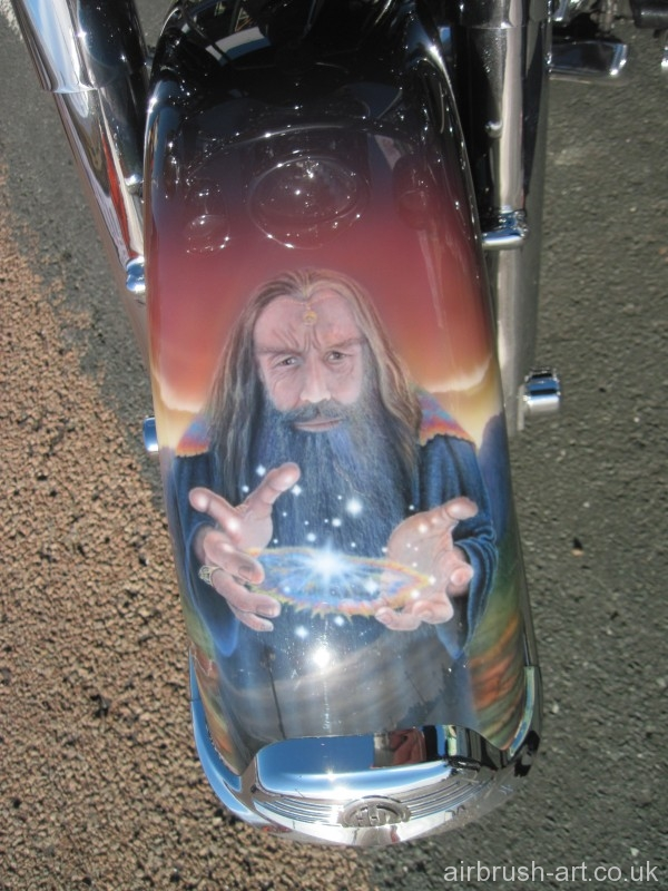 Merlin performing magic on the front mudguard of the custom painted motorcycle.