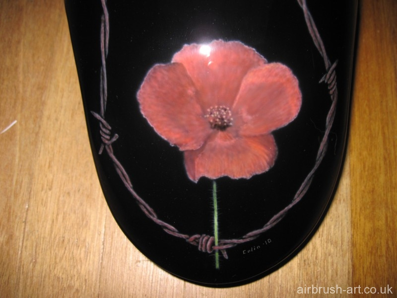 A red poppy on the front Harley mudguard with rusty barbed wired.