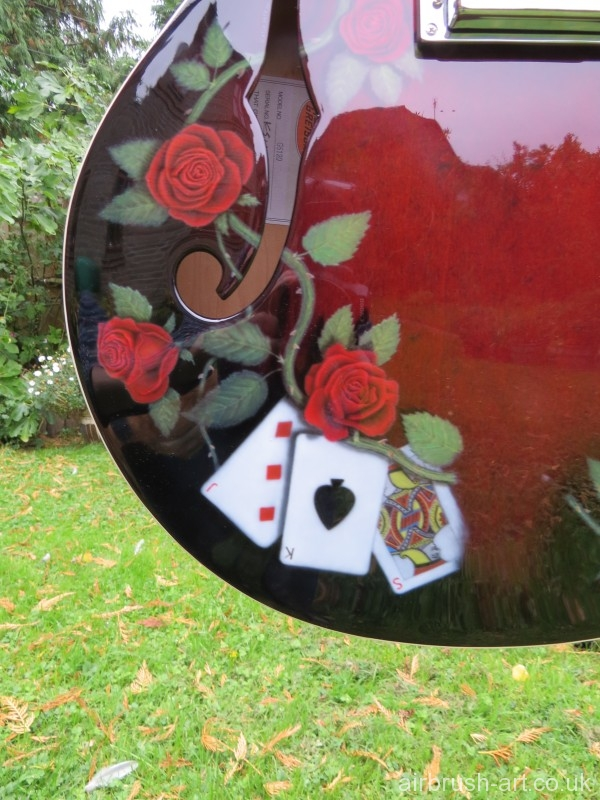 Roses and playing cards on airbrushed guitar.