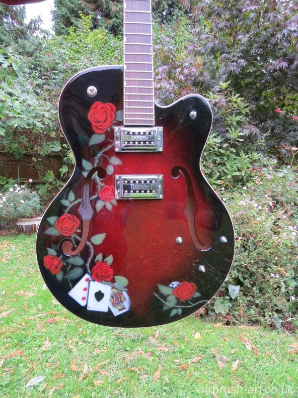 Gretsch guitar airbrushed with roses and playing cards.