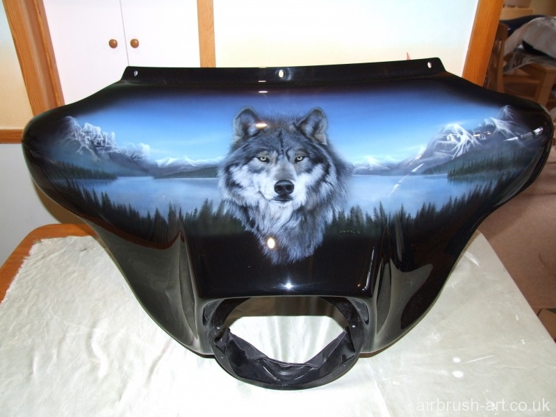 Airbrushing on Harley batwing fairing of North American lake scene with wolf as centre piece.