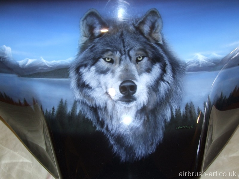 close up of airbrushed wolf with distant snowcapped mountains and lake in background.